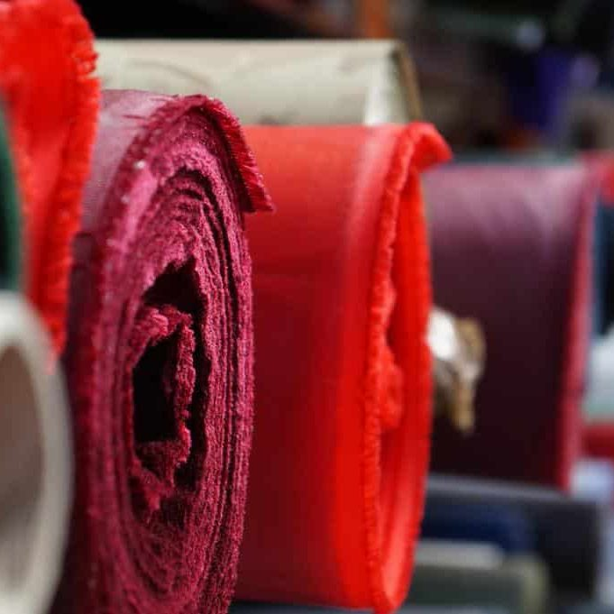 Rolls of different coloured textile material on a warehouse shelf.